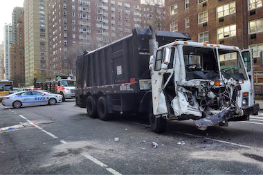 The garbage truck collided with another vehicle near Columbus Circle about 5:30 a.m., witnesses said.