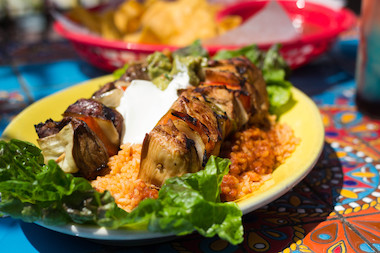 A dish of skewers of chicken and beef that features all the colors of the Mexican flag.