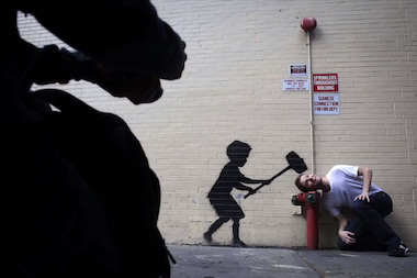 "A fan poses with a Banksy mural that was painted in New York City during October, 2013. The image was shared by the artist in a video prepared for the 2014 Webby Awards, for which he won ""Person of the Year."""