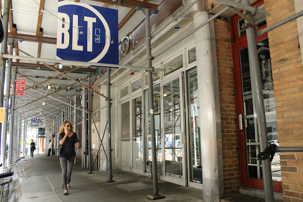 The owner of BLT Fish says that it loses more than $50,000 a month in revenue because of scaffolding on the facade of its building.