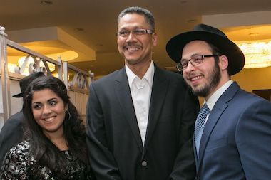 UPS worker Terry Spiers (middle) stands with Chana Simon (left) and Zevi Goldin (right), at the young couple's engagement party. The two met because of Spiers' suggestions to Goldin and Simon's family for the past two years.