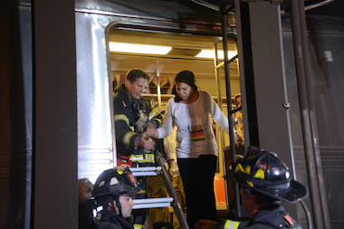 Firefighters help a passenger climb down from the derailed F train in Queens, May 2, 2014.