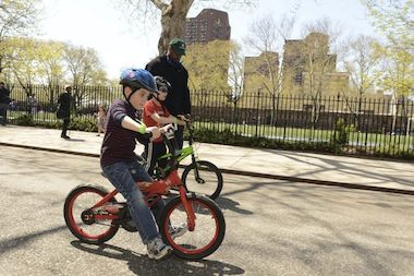 A boy learns to ride a bicycle at a free lesson hosted by the NYC Parks Department and Bike New York.