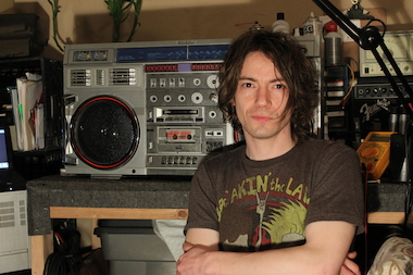 Nick Vivid, pictured, poses with a Conion C-100F vintage boombox he is repairing in his Orchard Street studio on May 22, 2014.