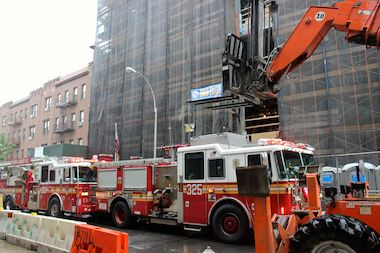 Fire trucks at the scene of an incident in Sunnyside where a worker fell down an elevator shaft to his death at the site of the future P.S. 313 on June 5, 2014.