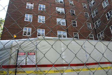 Workers are replacing existing deterioated parapets with roof railings at Red Hook Houses West. Since the parapets contain asbestos, the materials need to be removed and safely disposed before rebuilding can begin, NYCHA officials said.