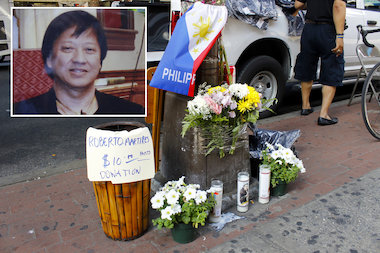 The memorial put up for Robert Martires includes candles, the flag of the Philippines and baskets to help raise money for his funeral.
