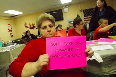 A protester holds up a sign during a December community meeting in hopes of saving the Swinging Sixties Senior Center.