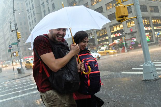 People grabbed umbrellas and ran for cover during torrential rains on July 15, 2014.