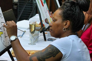 "An artist at a recent ""Painting and Sipping"" event. The monthly painting event is held at Therapy Wine Bar, where people can drink and channel their inner artist."