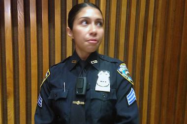 Sergeant Andrea Cruz demonstrates the VieVu LE3, a pager-size camera worn on the front of an officer's shirt.