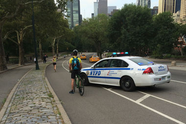 An officer pulls over a cyclist in Central Park. Tickets for cyclists in the 24th Precinct went way up last month, police said.