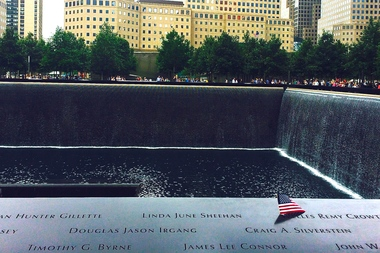 A flag sits atop one of nearly 3,000 names etched into the massive 9/11 Memorial pools.