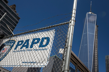 A Port Authority Police Department banner is posted on a barbed wire fence outside One World Trade Center on March 21, 2014.