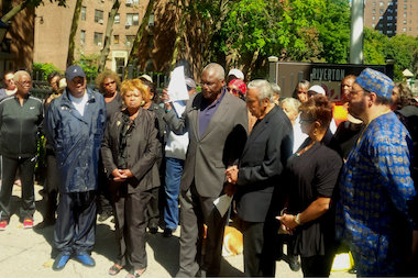 State Assemblyman Keith Wright (middle) and other elected officials stand in front of the Riverton Complex on 135th Street and Fifth Avenue as they announce the lawsuit. Randreta Ward-Evans, president of the tenant's association, stands to the right of the assemblyman.