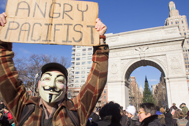 A masked man holds a sign in Washington Square Park before the Millions March NYC on Dec. 13, 2014.