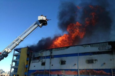 Flames shoot out from the roof of a warehouse at 5 N. 11th Street.