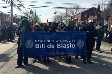 Volunteers marched with de Blasio's banner without the mayor present. He arrived half an hour late to the parade.