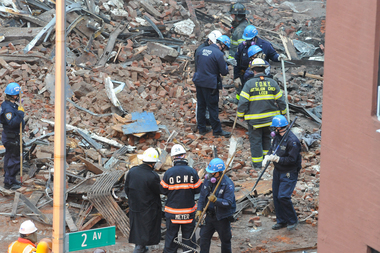 Workers shift through rubble the day after an explosion leveled an apartment building on 2nd Avenue and 7th Street on March 27, 2015.