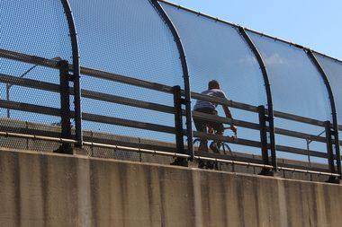 A cyclist rides over the Pulaski Bridge.