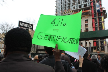 A rallier holds a sign reading