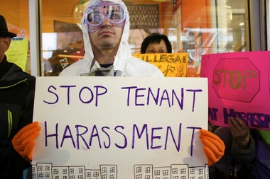 Seth Wanderman, 41, a rent-stabilized tenant who has lived at 210 Rivington St. for the past 15 years, holds up a sign during a press conference announcing the Mahfar Tenants Alliance's lawsuits against landlord Samy Mahfar of SMA Equities on April 20 in front of the Cooper Square Committee's office on East Fourth Street.