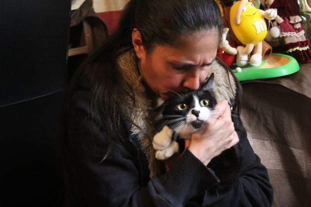 A woman ran into her burning home to rescue her cat, Slick, 3, she said.
