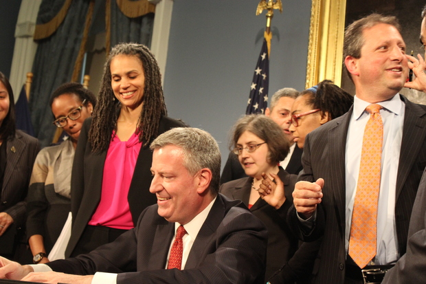 Mayor Bill de Blasio signs a bill into law banning the use of credit checks in hiring decisions by most employers. The mayor is flanked on the left by his chief counsel Maya Wiley and on the right by one of the bill's sponsors, Brooklyn Councilman Brad Lander.