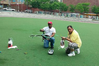 John Feliciano (right) and a friend work on their model helicopters at an Uptown school yard.