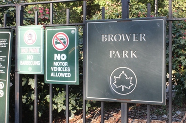 A sign outside of Brower Park. A man walking his dog found a dead woman in the park Saturday afternoon, police said.