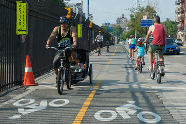 Cyclists and pedestrians make their way down the Brooklyn Greenway along Columbia Street.