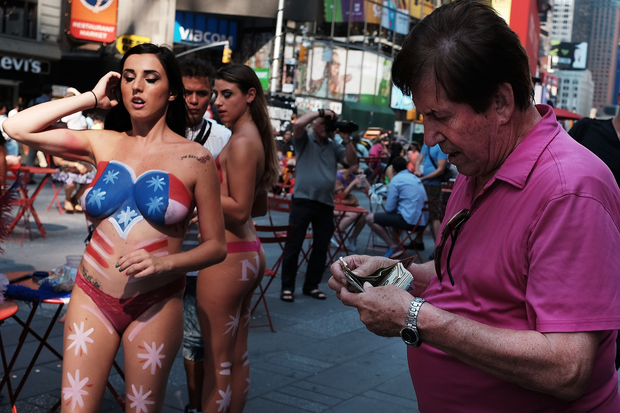 A man prepares to tip a semi-nude model after posing for a picture in Times Square on August 18, 2015. Mayor Bill de Blasio has announced that the city is addressing the issue of topless and painted women who pose for pictures in Times Square while soliciting tips.
