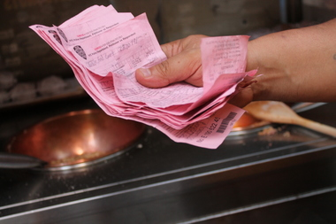 Nut seller Humberto Fernandez, 45, shows his stack of tickets that are mostly for being too close to a crosswalk.