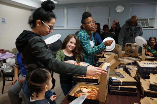 Shelter residents enjoy pizza from Uno Grill as part of a bet between Chicago and New York's transit agencies.