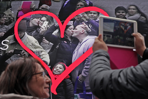 Tourists gather to show their affection for each other in front of the Revlon's Kiss Cam in Times Square. The company temporarily turned off the live cam after police said several women had been groped.