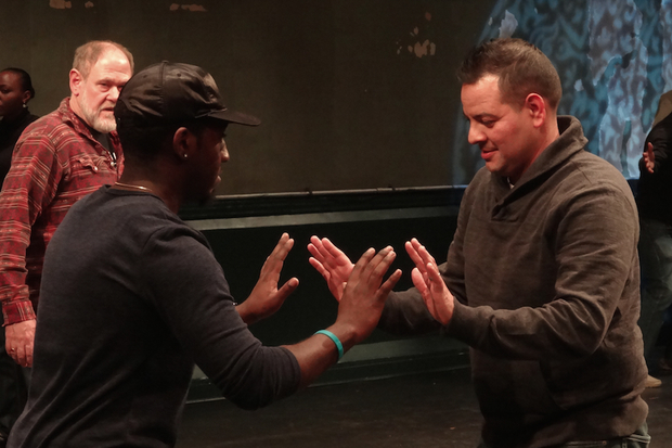 Civilian Joshua Tucker and police officer John Velez play a theater game at a meet-and-greet dinner for the ensemble last week. Terry Greiss stands behind them.