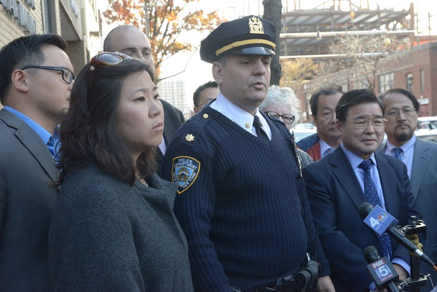 The 109th Precinct's Deputy Inspector Thomas Conforti stands with elected officials in Flushing Monday to announce a new enforcement for pedestrians following the death of a woman last week.