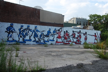 A 2011 photo of 201 Ninth St. shows a mural by the street artist General Howe that references the Revolutionary War's Battle of Brooklyn. The School Construction Authority wants to build a 180-seat pre-K center on the land, but some historians believe the site is the final resting spot for the Maryland 400. They want a memorial park there instead of a school.