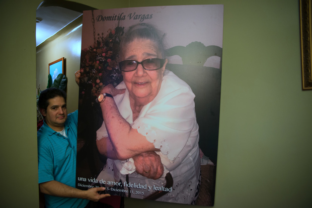 Herman Vargas holds a giant photo of his mother displayed at her wake in Manhattan.  The words