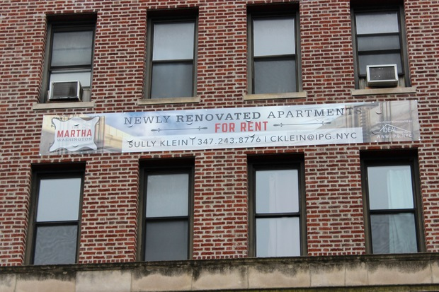 A banner from Ideal Properties Group advertising newly renovated rental apartments hangs on 85 Eastern Parkway in Prospect Heights.
