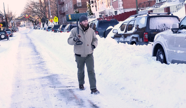 A man armed with a shovel walks down a street in Woodside, Queens a day after a blizzard dumped up to 34 inches of snow in parts of New York City.