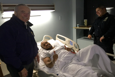 Police Officer Sherrod Stuart, seen here with Police Commissioner William Bratton, gives the thumbs up from his hospital bed.