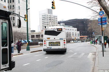 A B38 bus crosses from the curbside stop on the Adams Street service road to the main roadway to make a left turn at Fulton Street as a B41 approaches.