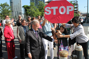 Residents and councilman Jimmy Van Bramer erecting a cardboard stop sign at the intersection of 5th Street and 47th Avenue in Hunters Point.