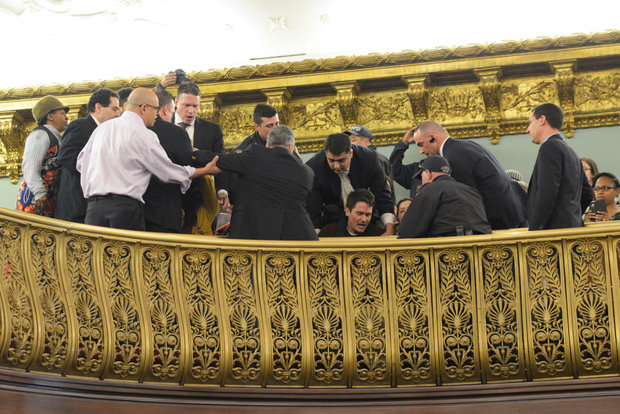 Security and police attempt to escort protesters from the balcony at the city hall chambers during a vote on the mayor's rezoning plan on March 23, 2016.