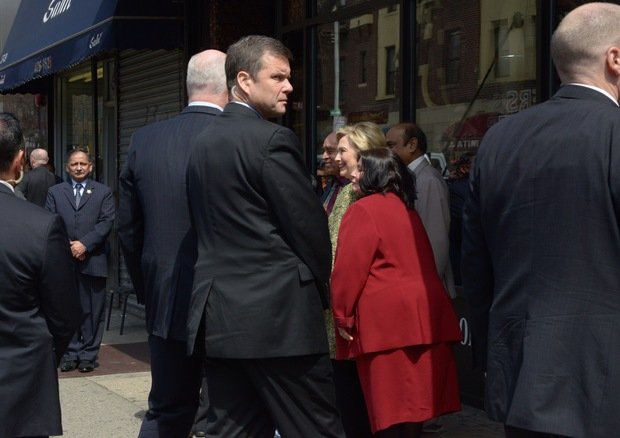 Hillary Clinton poses with the owners of the Jackson Diner while flanked by multiple security guards, who closed off 74th Street.