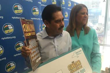 Eduardo Reyes (left) with Yolanda Vega (right) of the New York Lottery. Reyes won $7 million with a Golden Ticket scratch off card, but waited a week to cash in because he couldn't take a day off work