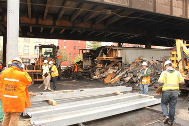Metro-North workers wield temporary support beams to repair damages after a massive blaze occurred Tuesday night under the tracks in East Harlem between East 117th and 118th streets. May 18, 2016