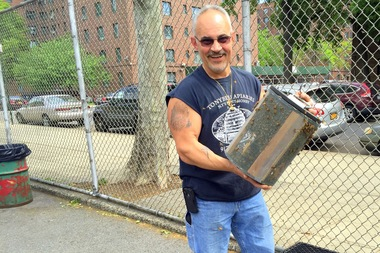 Det. Anthony Planakis removed a 5-pound swarm of bees from a playground fence in Parkchester on Thursday.