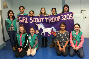 The Girl Scout Junior Troop 3205 (only ten members shown here) has collected nearly 500 signatures to add a red blinking light and rumble strips to the intersection of Seaman Avenue and 218th Street.